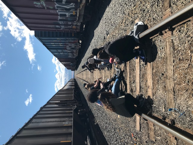 girls sitting in empty train yard
