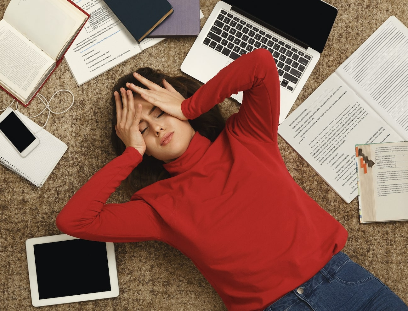 woman-in-red-laying-with-books-stressed